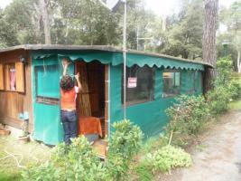 Kleiner Holzbungalow mit integriertem Wohnwagen
