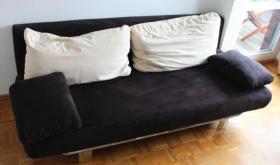 Komfortables Doppelschlaf-Sofa (schwarz) mit hellen Kissen