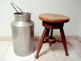Milchkanne und Holzschemel