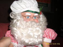 Weihnachtsmann, der Kuchen rührt und Kopf bewegt
