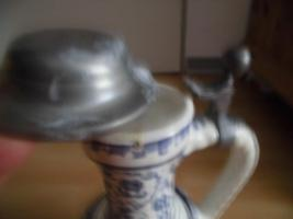 Foto 2 Ulmer-Keramikkanne;blau dekoriert, man kann vier Personen sehen;heil, nur der Deckel ist ein Problem
